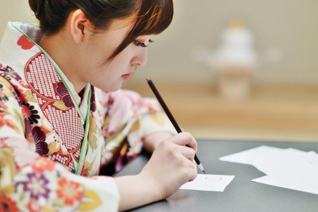 毛筆で何かを書く女性の写真